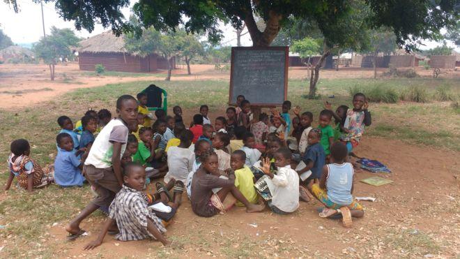 bambini africani seduti sotto un albero