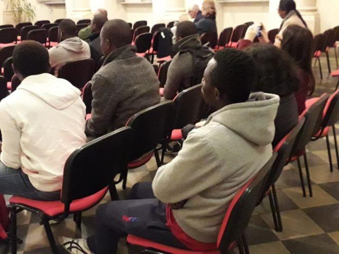 ragazzi immigrati ascoltano una conferenza